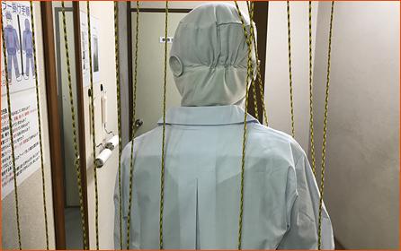 除電カーテンをくぐり、 作業着の付着物を除去